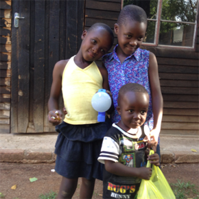 African family holding VELUX solar lamps.