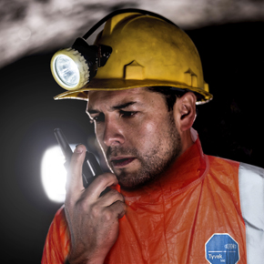 Portrait of a miner working at the mine and talking on a walkie-talkie