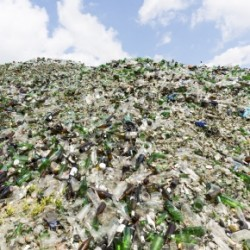 Glass waste for recycling in a recycling facility. Different glass packaging bottle waste. Glass waste management. Process of waste glass into usable products. Pile of  different bottles.