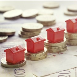 Minature houses resting on pound coin stacks concept for property ladder, mortgage and real esteate investment