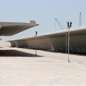 The 60 m long and 25 m wide bridge spans are stored and left to set in the desert before being transported to the bay.