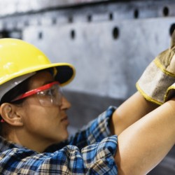 Female manual worker drilling holes in sheet metal in factory