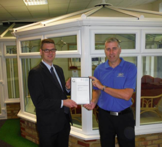 Simon Beer (left) presents Mark Page of R&M Windows & Conservatories with the first Q-Mark Conservatory Installation Scheme certificate